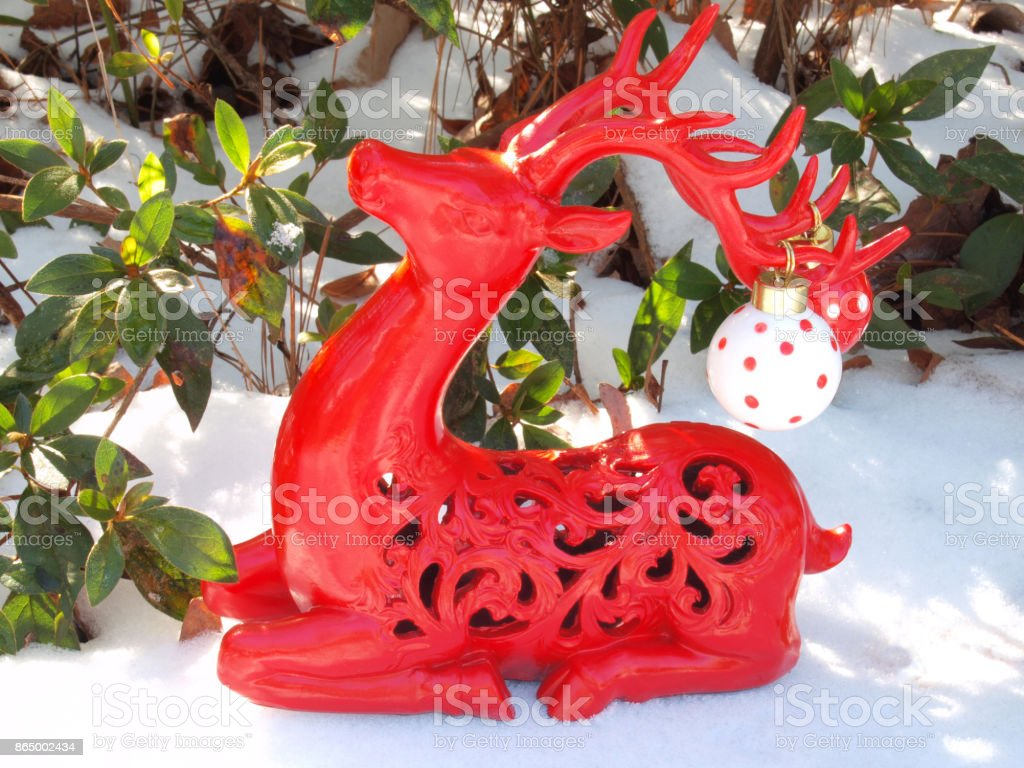 Red Deer Figurine with Ornaments Sitting in Snow stock photo