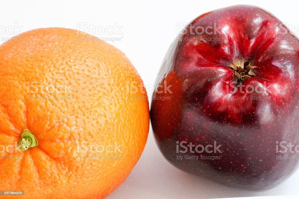 Red delicious apple and orange side by side stock photo