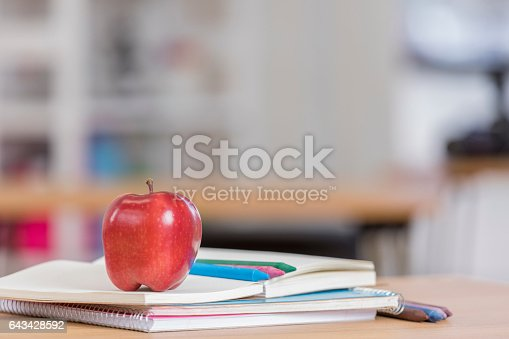 istock Red delicious apple on top of books in classroom 643428592