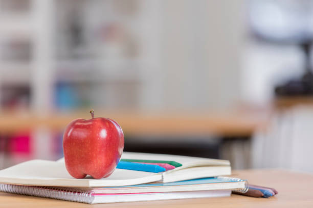 Red delicious apple on top of books in classroom stock photo