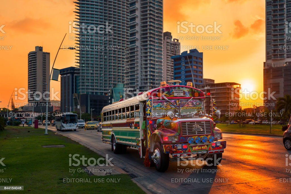 Red Devil bus in Panama City with modern building on the background at sunset, in Panama. stock photo