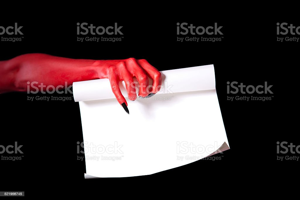 Red devil hand holding paper scroll stock photo