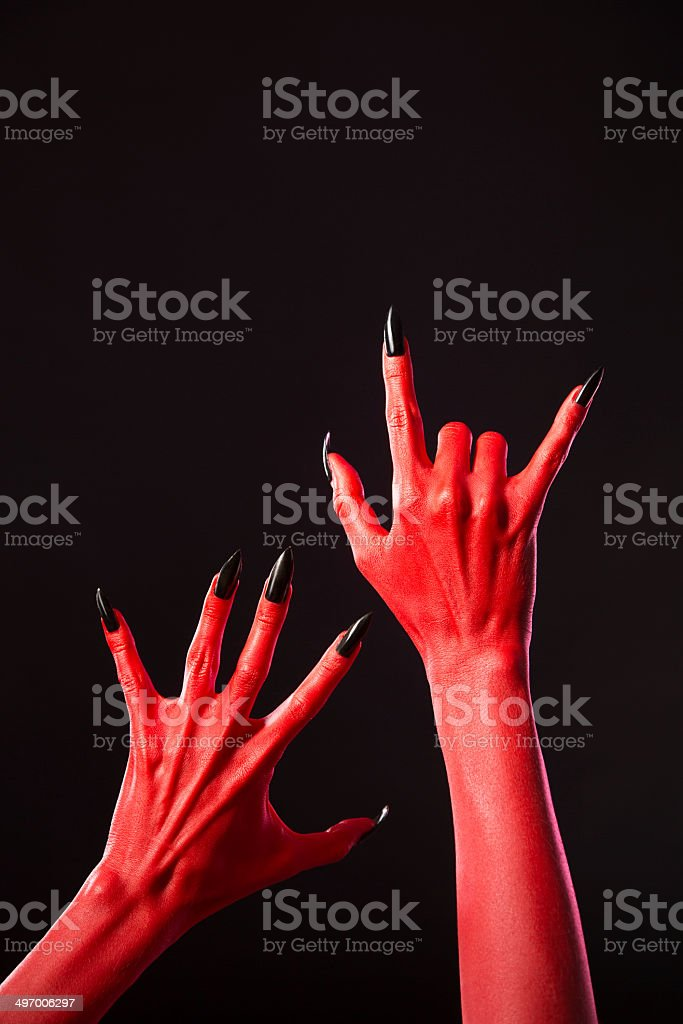 Red devil hands with long black nails, real body-art royalty-free stock photo