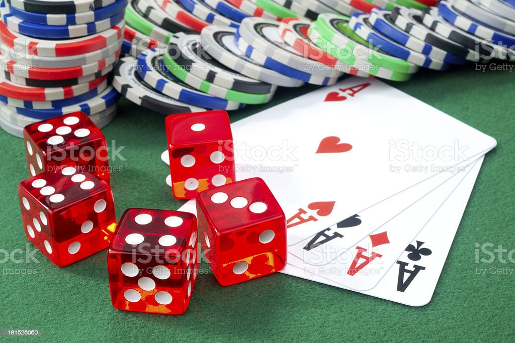 Red dice, four aces and chips on a green felt royalty-free stock photo