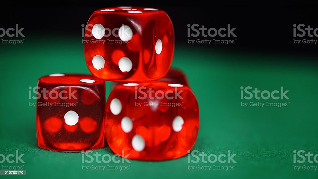 Red dice on a green felt stock photo