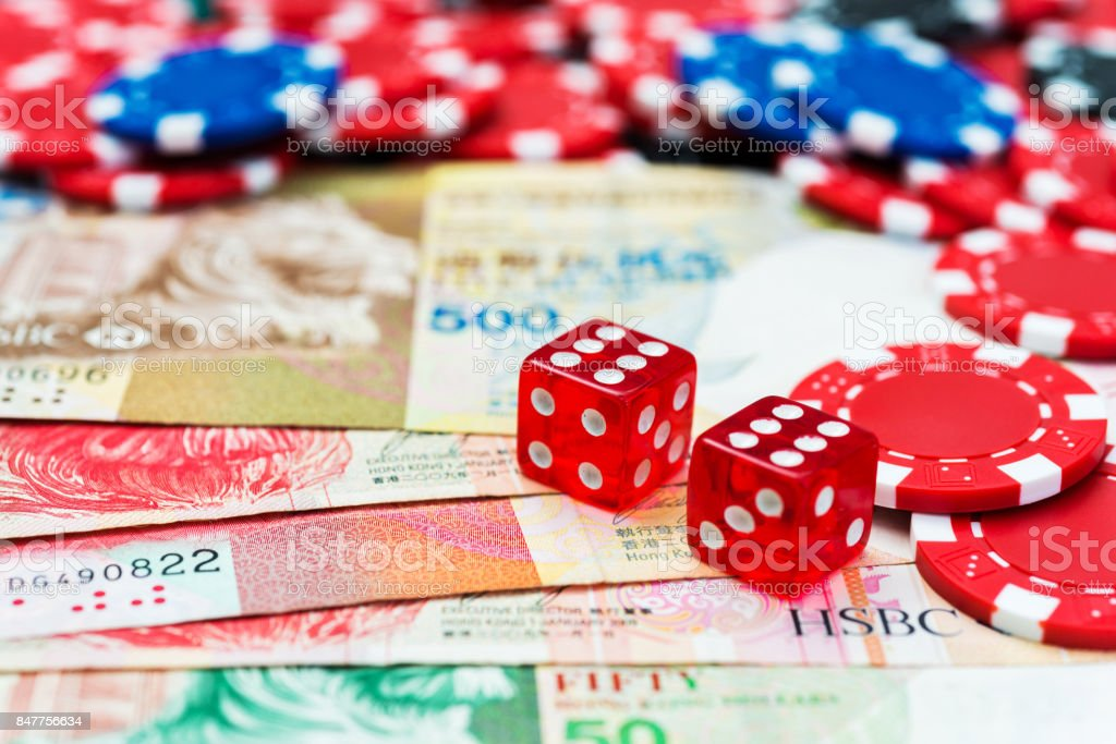 Red dices and hong kong currency on the table stock photo