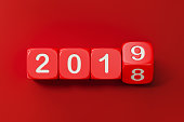 Red dices are rolling from 2018 to 2019. Numbers are engraved on dices. Dices are lit from the upper left corner of the composition and casting shadows on red background. New year and change concept.  Horizontal composition with copy space.