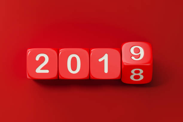 Red Dices are Rolling From 2018 to 2019 Red dices are rolling from 2018 to 2019. Numbers are engraved on dices. Dices are lit from the upper left corner of the composition and casting shadows on red background. New year and change concept.  Horizontal composition with copy space. 2018 stock pictures, royalty-free photos & images