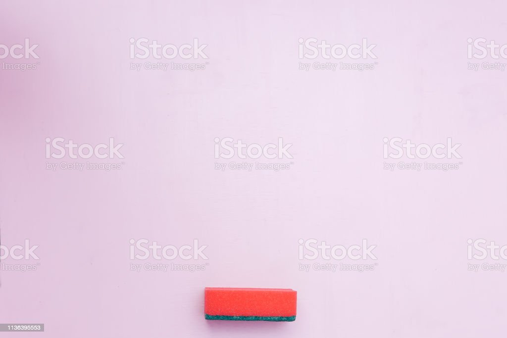 A red dish wash kitchen sponge on pink background copy space flatlay...