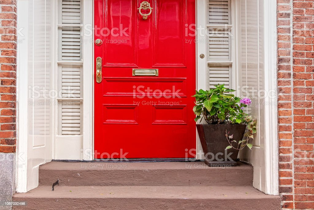 red door and potted plant on the steps stock photo