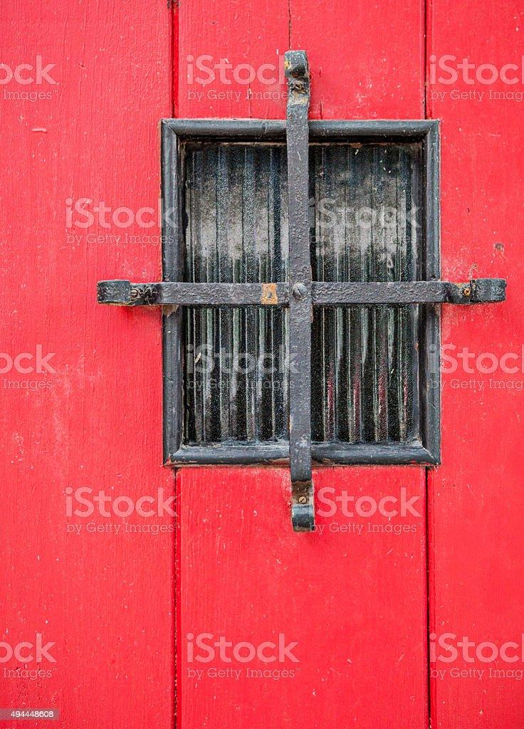 Red Door Barred Window stock photo