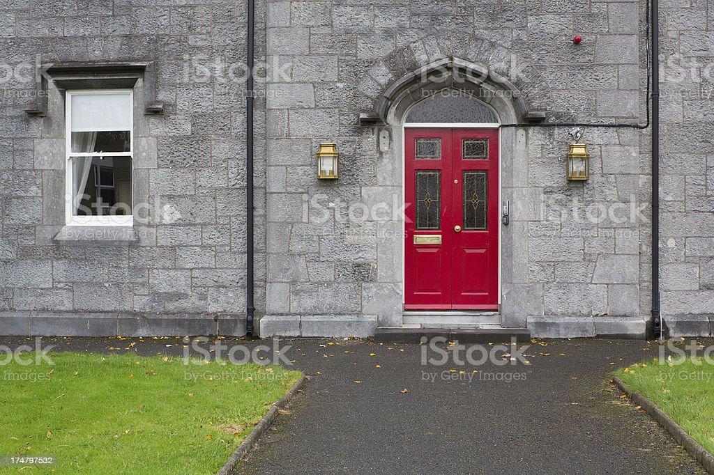 Red door in grey stone building royalty-free stock photo