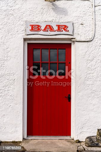 Sign above the red door at the entrance to an Irish pub.