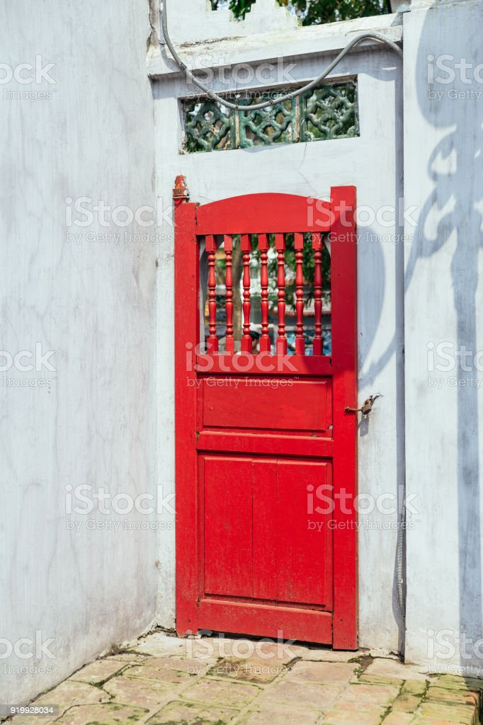 Red door of Ngoc Son Temple entrance with green trees in the background from Red Bridge at Hoan Kiem Lake in Hanoi, Vietnam. stock photo