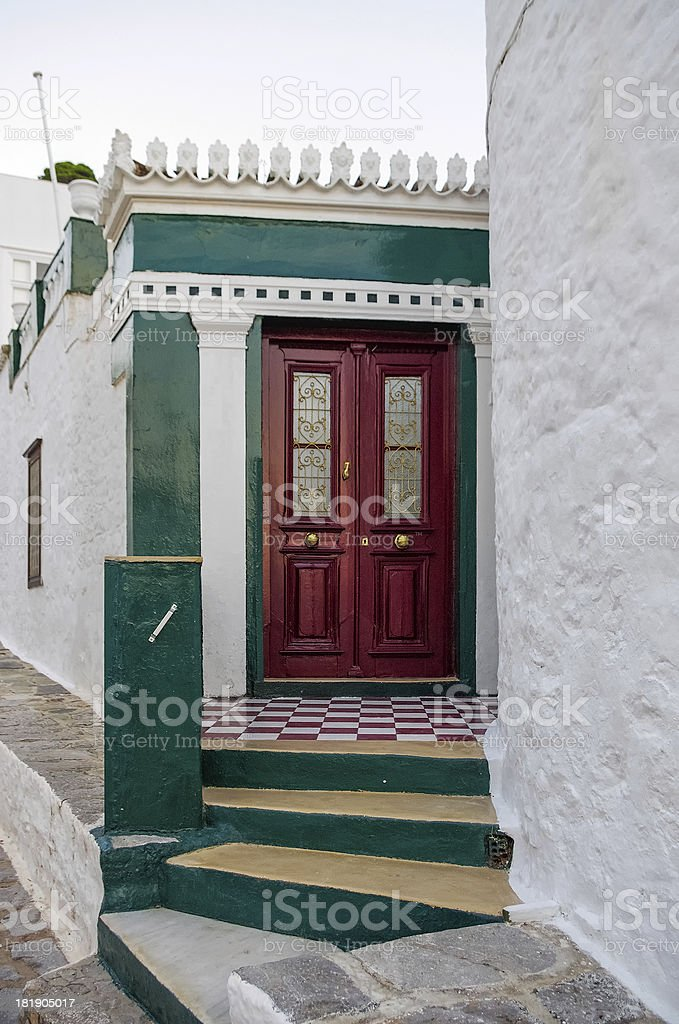 Red door Red door on a white and green wall, in Hydra island, Greece Architecture Stock Photo