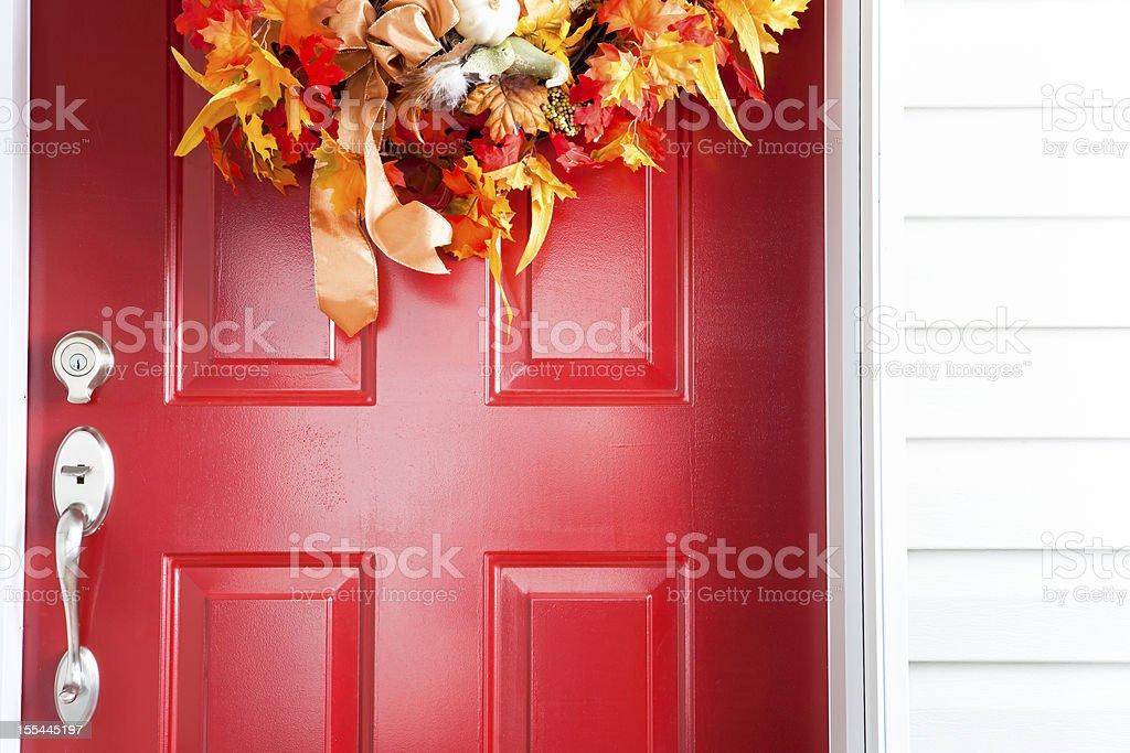 Red door with autumn wreath stock photo