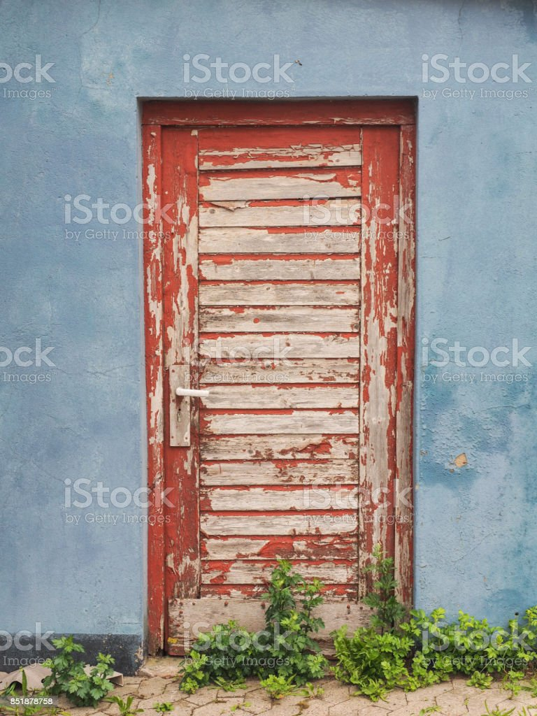 red door with paint flaking off in a red wall stock photo