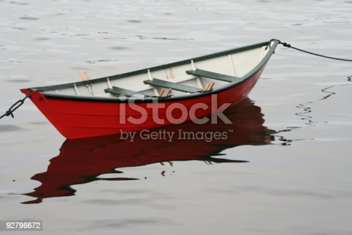 Red dory with reflection in calm water moored with two lines.