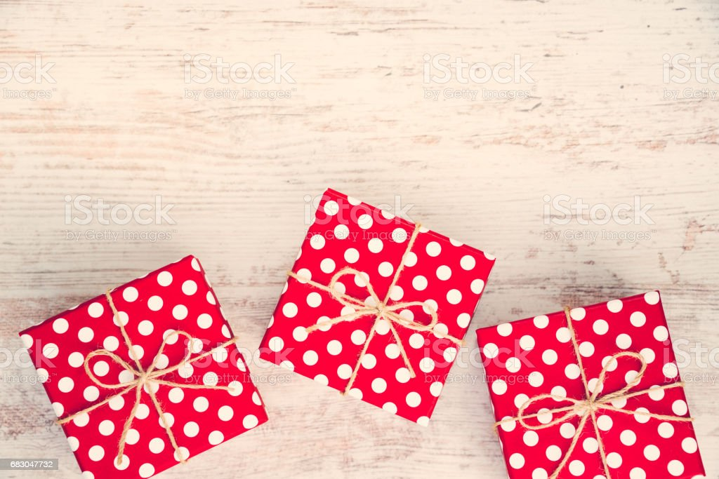 Red dotted gift boxes scattered over white wood background. foto de stock royalty-free