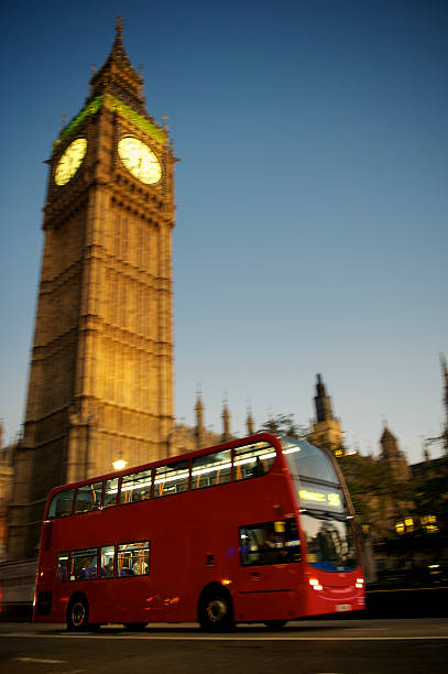 Red Double Decker Bus Drives by Big Ben London stock photo