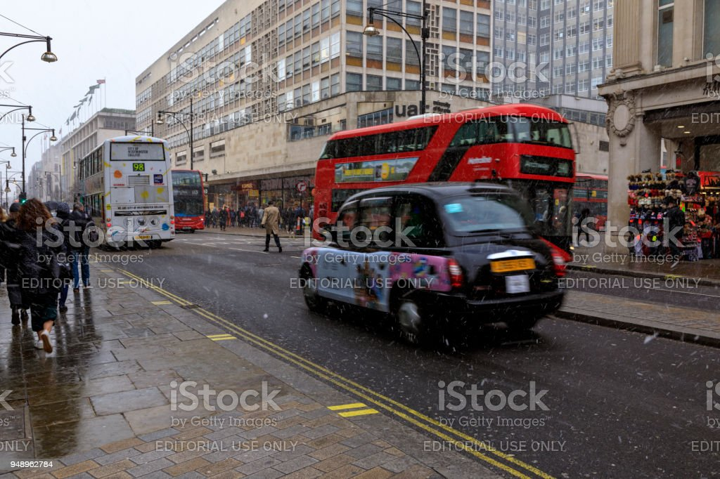Red double-decker bus and taxi cab in London city center street traffic stock photo