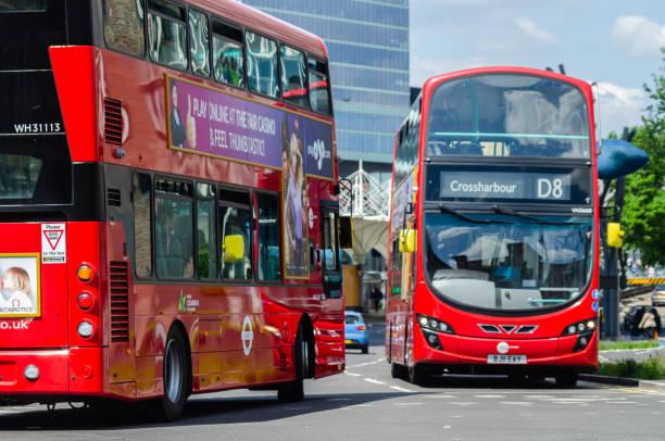 Barramento de dois andares vermelho que conduz abaixo da rua em Londres do leste, um veículo de transporte urbano britânico típico - foto de acervo