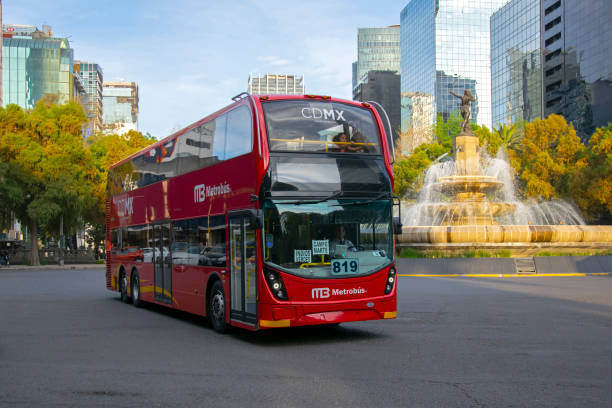 Red double-decker bus driving in a city center Mexico City, Mexico - 2nd January, 2019: Red double-decker bus Alexander Dennis Enviro500 driving in a city center. This bus was built by Alexander Dennis Limited (ADL) in United Kingdom in 2017. Today is a popular bus in Mexico City. On the back of the bus we see the Huntress Diana Fountain (Fuente de la Diana Cazadora). bus rapid transit stock pictures, royalty-free photos & images