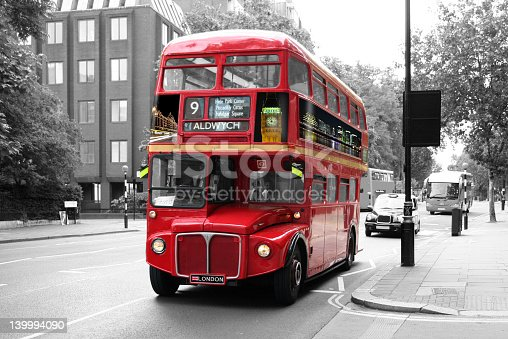 A traditional red double-decker bus isolated on a black and white background. The bus is on a moderately busy street in London and is directly followed by a black cab is a tourist coach. The picture is taken under a three-quarter angle from back right to front left.