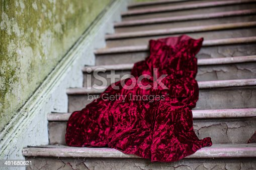 Red velvet wedding dress, on stairs of abandoned building.