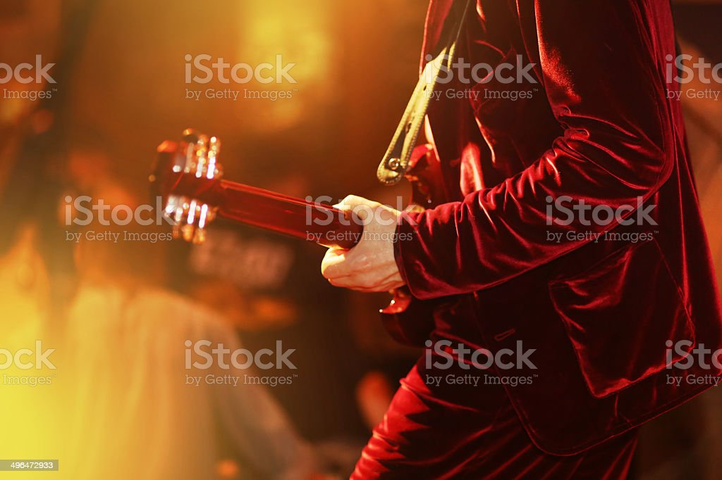 Red dressed guitar player on stage stock photo