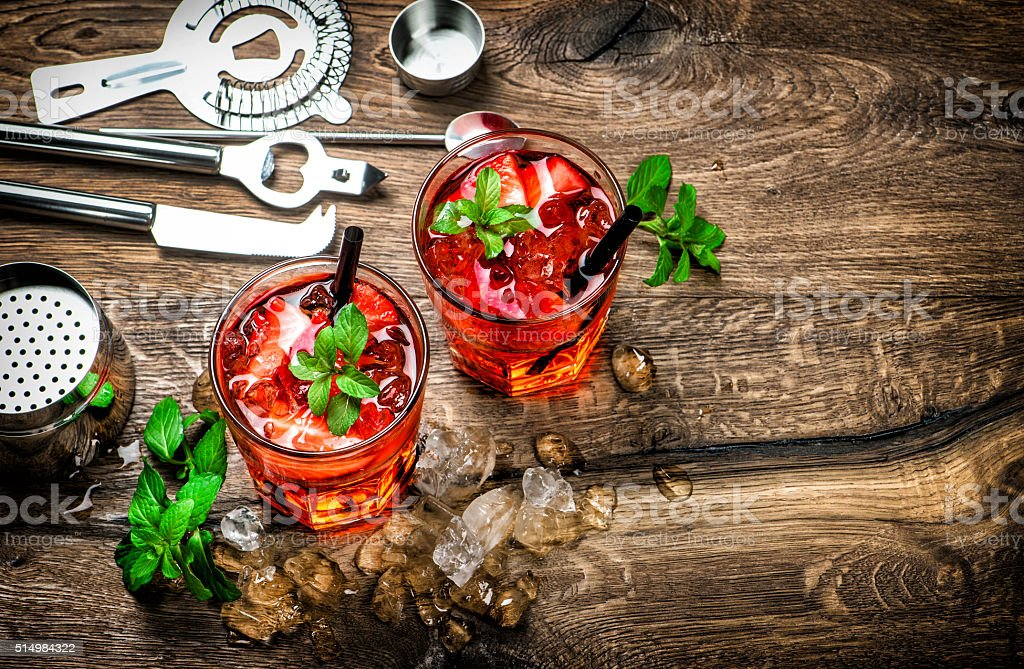 Red drink with ice, mint leaves and strawberry. Cocktail stock photo