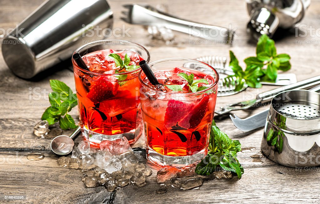 Red drink with strawberry, mint leaves, ice. Cocktail accessories stock photo