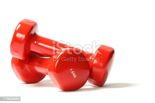 Red dumbbell weights on white background