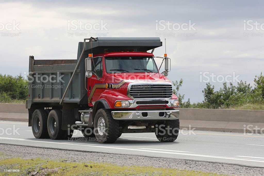 Red Dump Truck Travelling On Highway To A Construction Site stock photo