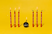 Red dynamite birthday candles burning on a bright yellow background
