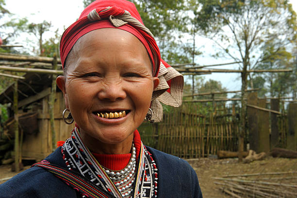 red dzao woman with golden teeth - gold tooth stock photos and pictures