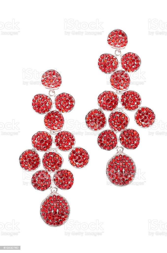 red earrings inlaid with precious stones on a white background stock photo