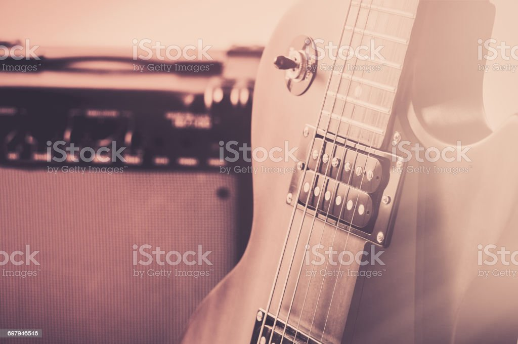 Red electric guitar and classic amplifier on a grey background stock photo