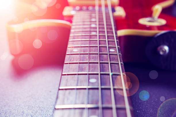 Red electric guitar close-up. Music concept. Vintage guitar on a background of sunlight and bokeh. stock photo