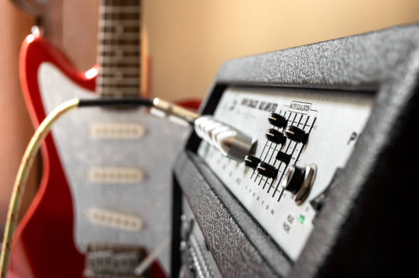 Red electric guitar plugged into large speaker. Close up of amplifier controls with blur effect on background. Playing guitar in home. stock photo