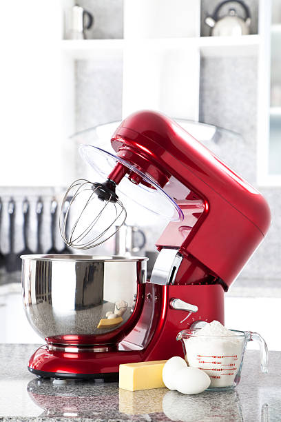 Red electric stand mixer on kitchen counter top A red electric stand mixer on kitchen counter top with eggs, butter and flour as ingredients for making a pie in the foreground. Focus in on the stand mixer while at the background can be seen a modern white kitchen out of focus.  electric mixer stock pictures, royalty-free photos & images