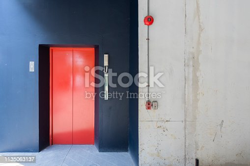 red elevator and black wall with fire alarm.