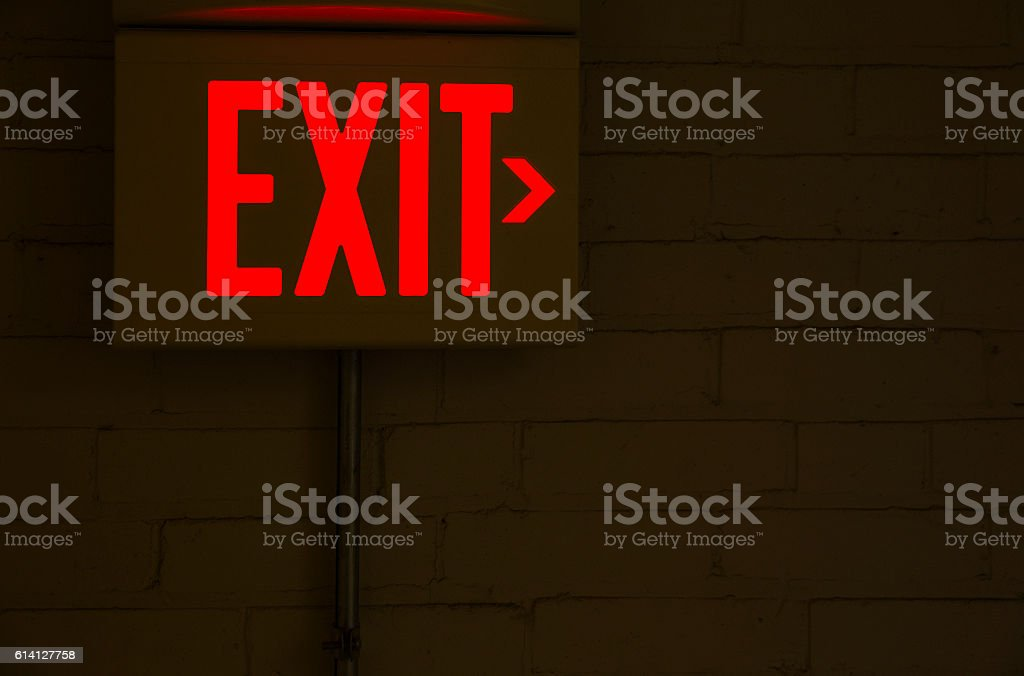 red emergency exit sign in the dark room stock photo