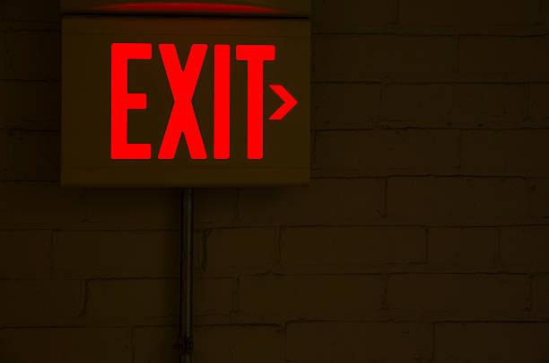 red emergency exit sign in the dark room - kinderlandverschickung stock-fotos und bilder