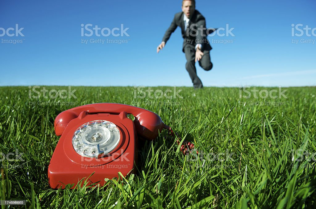 Red Emergency Phone in Meadow with Businessman Running royalty-free stock photo