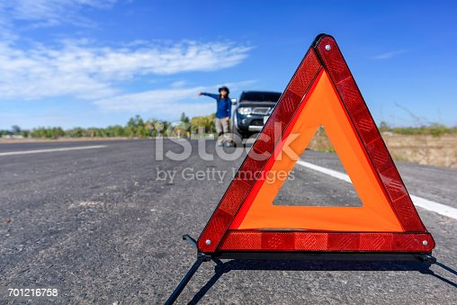 istock Red emergency stop sign and broken car on the road 701216758