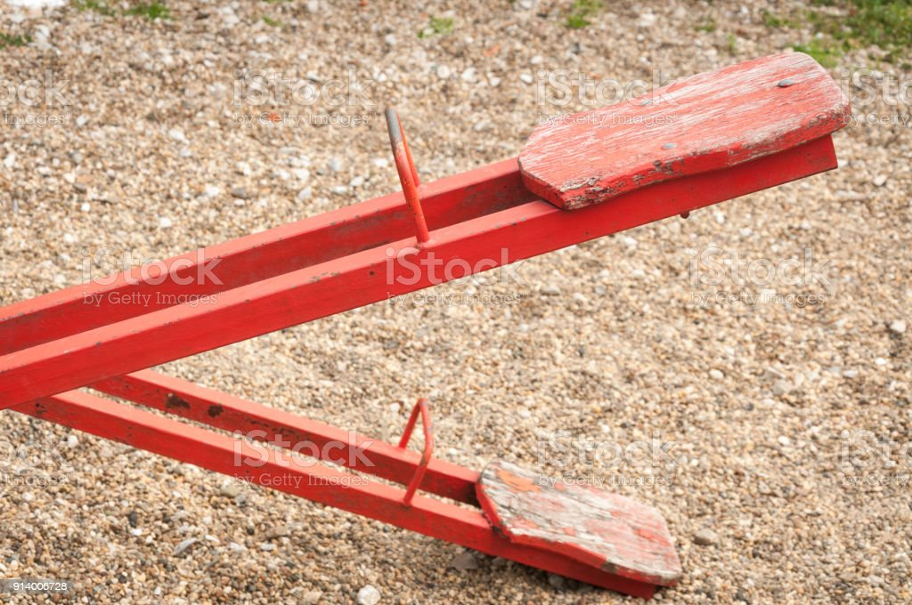 Red empty teeter seat on the playground without children to play, depression concept stock photo