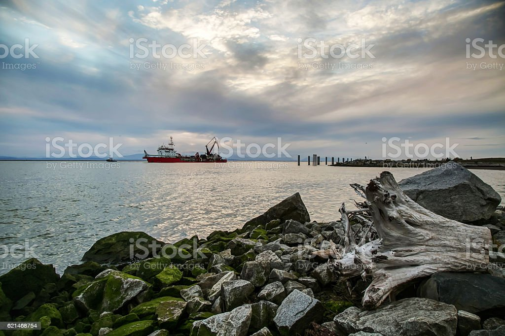red engineering ship on sea at sunset stock photo