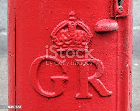 Typical red English telephone box in Mitcham, London Borough of Merton. Each Royal Mail post box has a royal cypher, indicating the King or Queen of the time. This photo shows the royal cypher for King George V, so the post box was installed between 1910 and 1936.