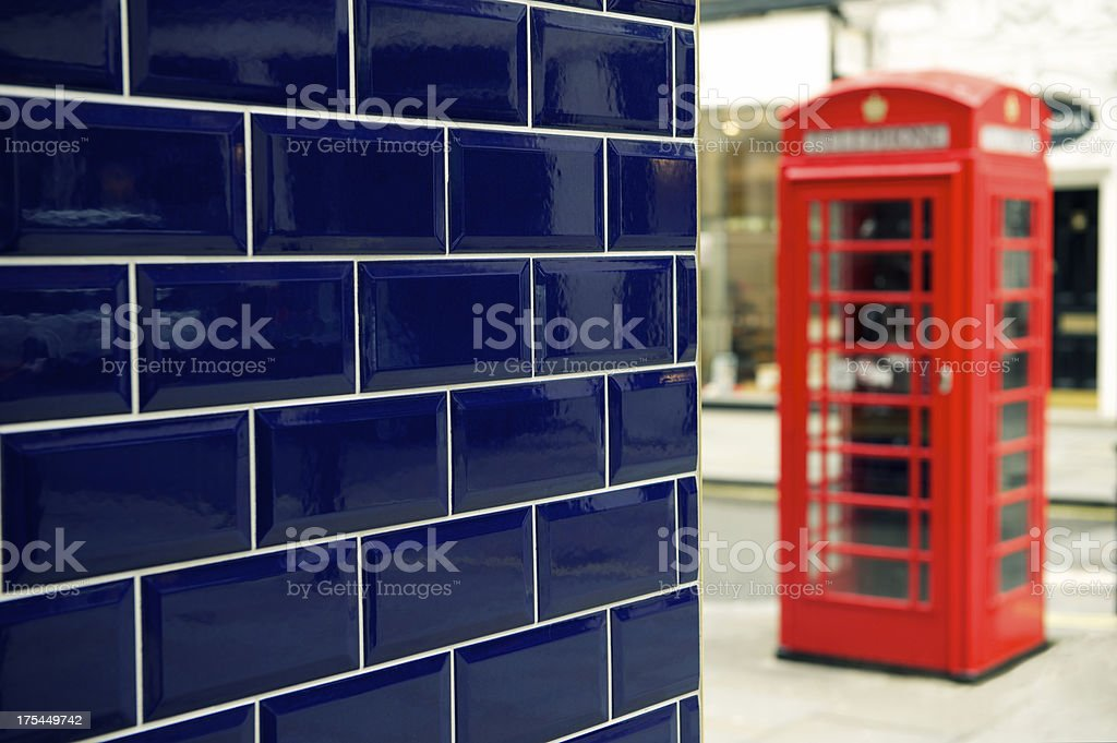 Red English Telephone Box Blue Tile Wall London stock photo